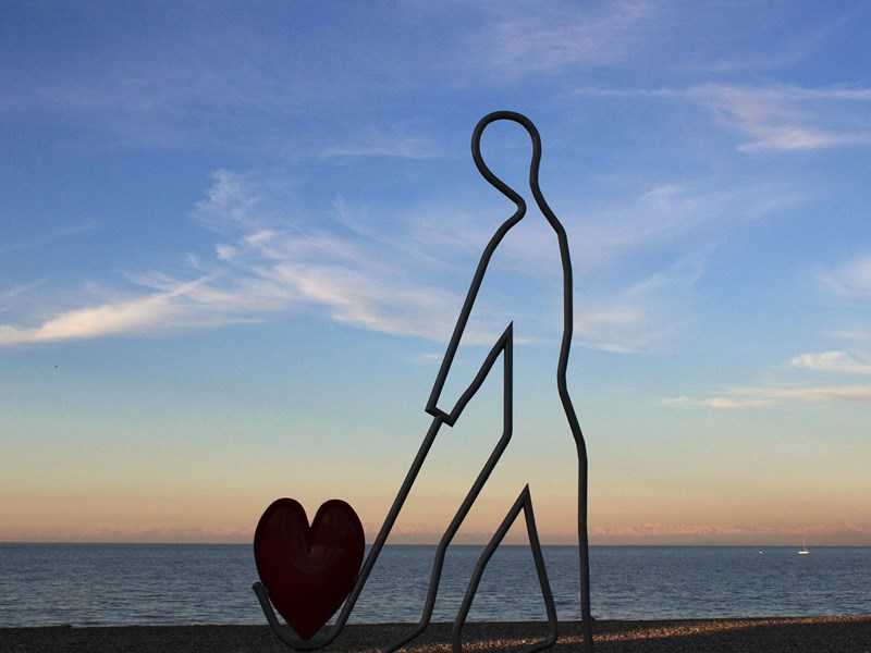 A sculpture of a man carrying a red heart <br />