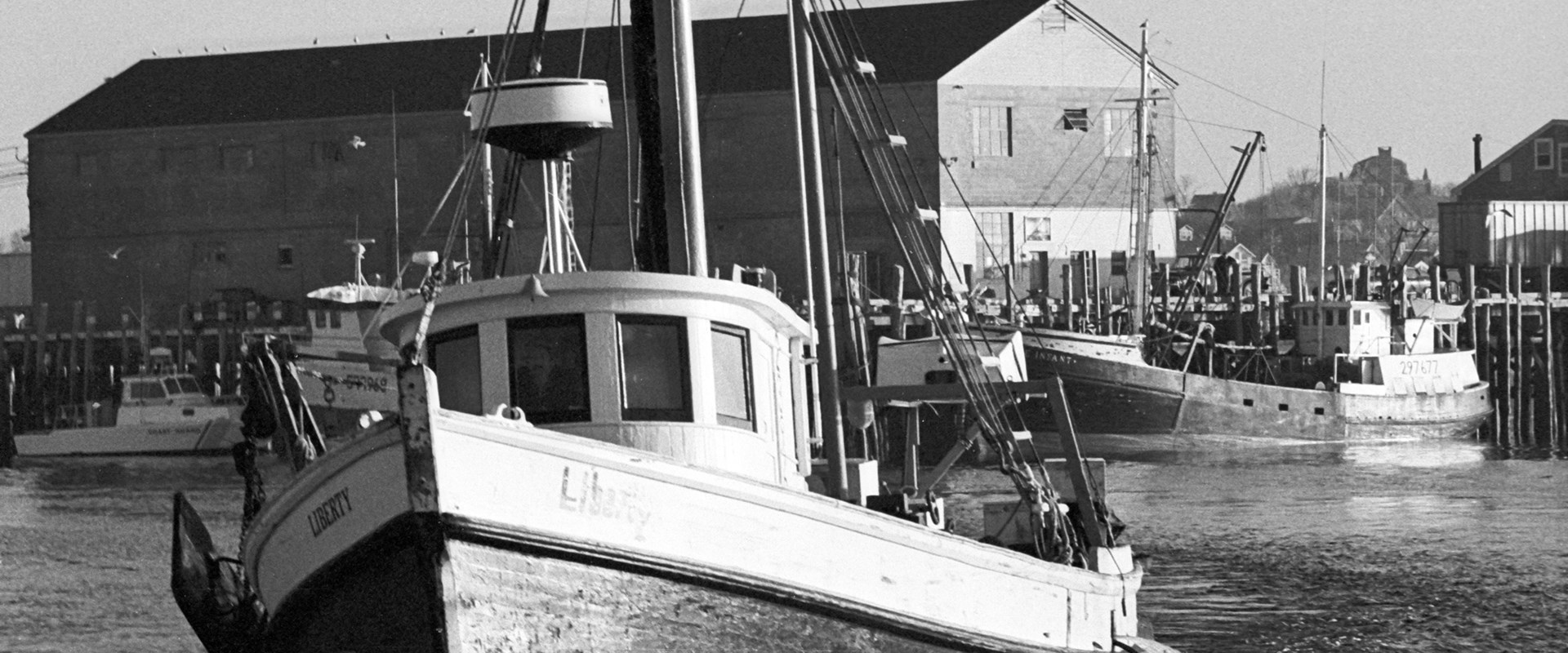 Liberty, a beautiful 1940 vintage wooden dragger owned by Norbert Macara, motors from Provincetown's MacMillan Wharf in a wash on morning sunlight across Cape Cod Bay. The large fish-packing plant on the wharf is gone today – as is the fishing fleet. <br />